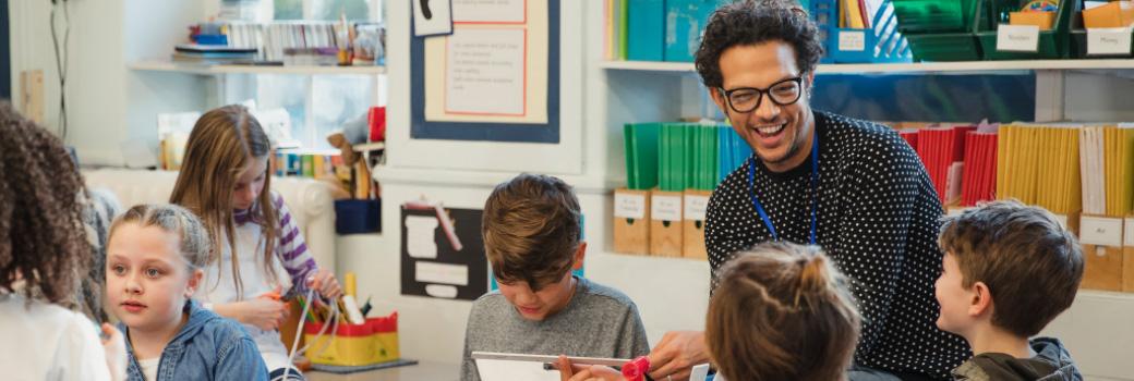 Primary school teacher helping pupils in their classroom