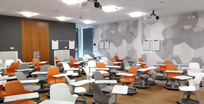 The Gannochy room showing wheeled 'node' chairs in different colours (orange, grey and white) each with a writing tablet and storage space underneath the seat.