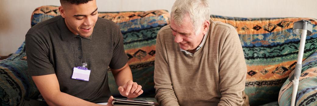 Housing officer sitting with elderly man, using iPad