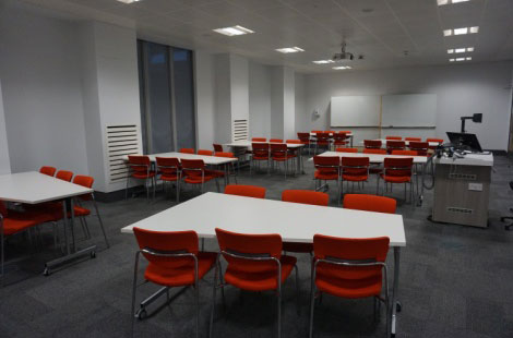 A room with trapezoidal white tables and six red chairs round each.