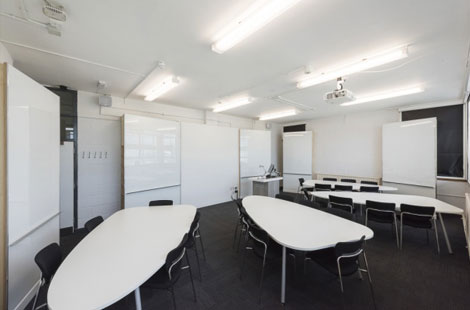 A room with large white plectrum shaped tables and black chairs. There are a lot of whiteboards on the walls.