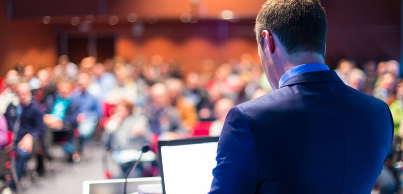 Male speaker at the front of a lecture theatre