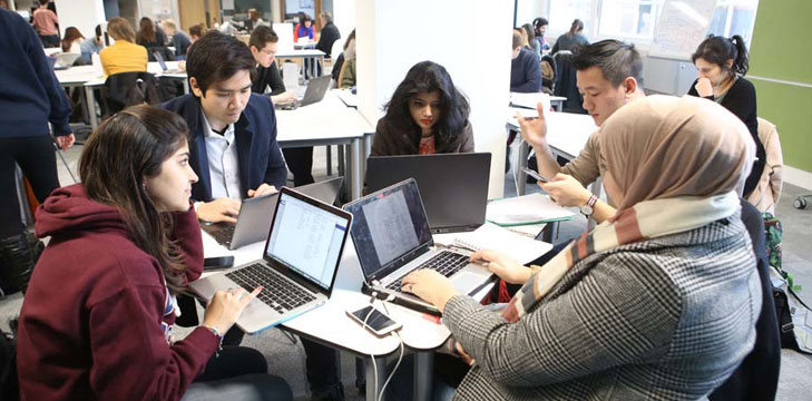 A group of students sitting at the small tessellated tables and using their own laptops and smartphones.
