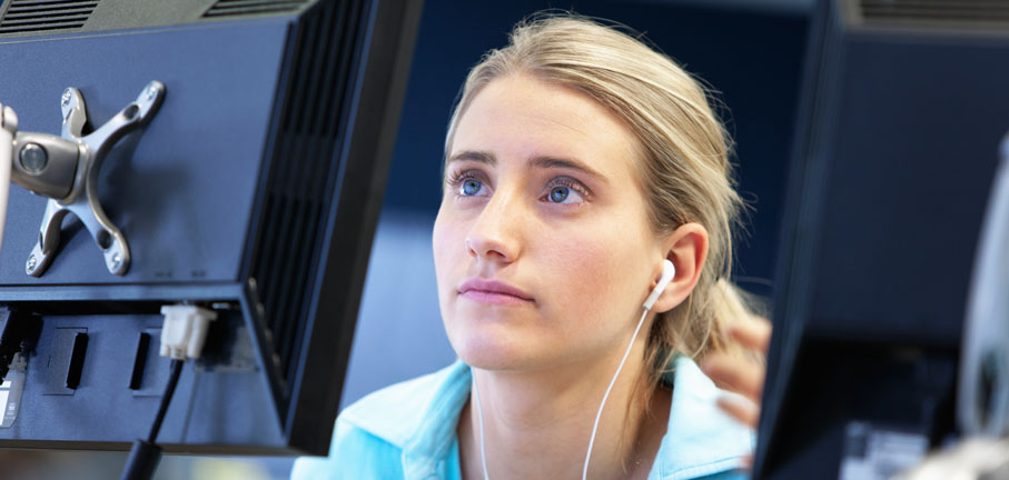 Student using headphones at a computer