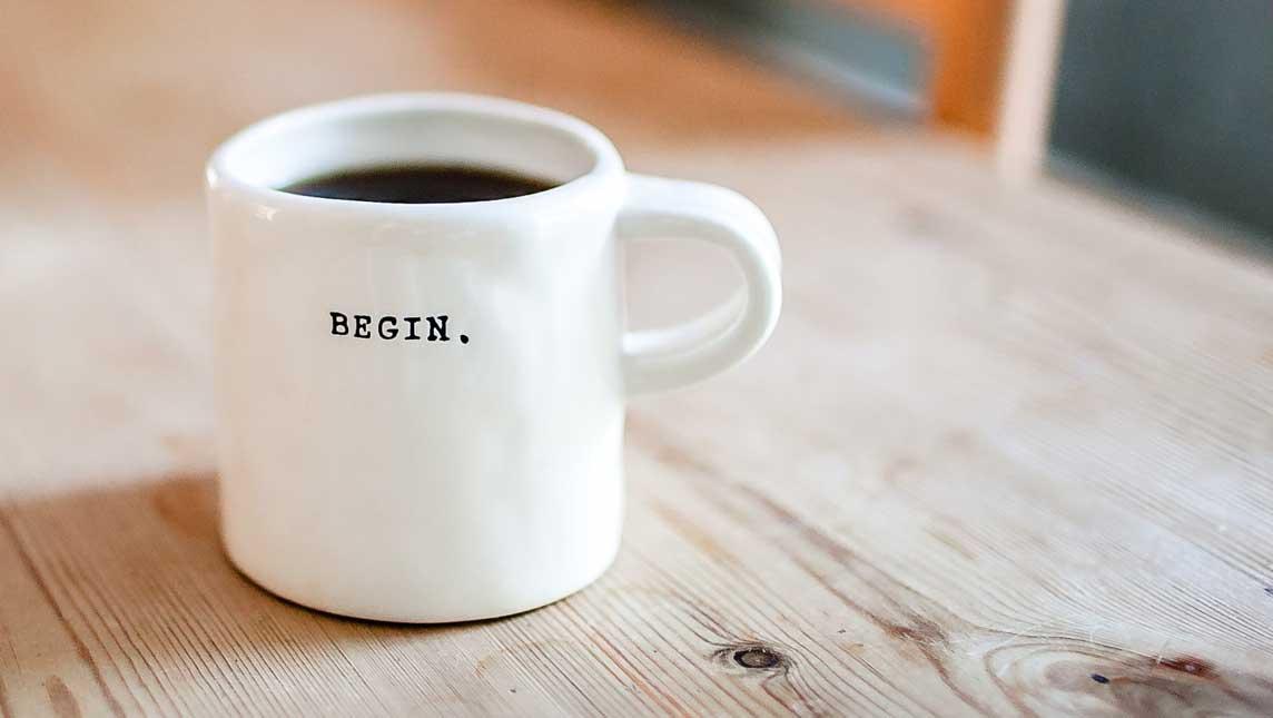 White mug with 'begin' written on it
