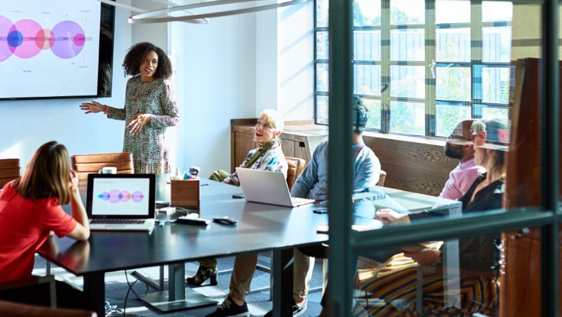 Female team leader standing in board room, providing feedback on digital strategy