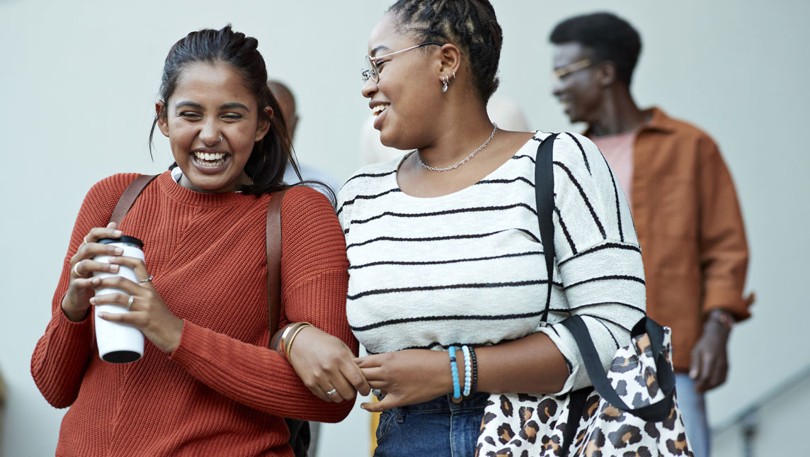 Friends smiling, walking arm in arm on campus