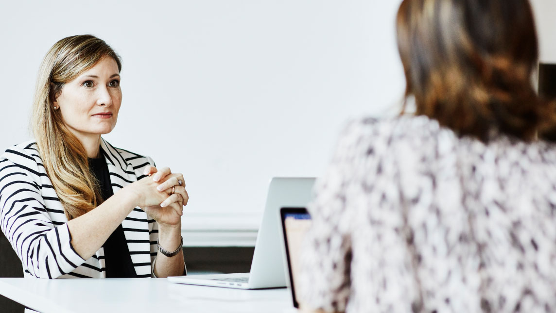 Woman interviewing new graduate in white office