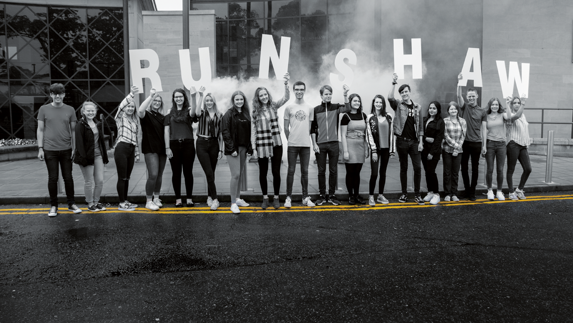 Students holding Runshaw letters above their heads on the road outside Runshaw College
