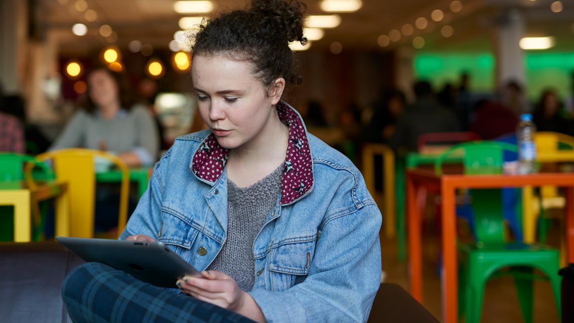 Student at Bath University using ipad on campus