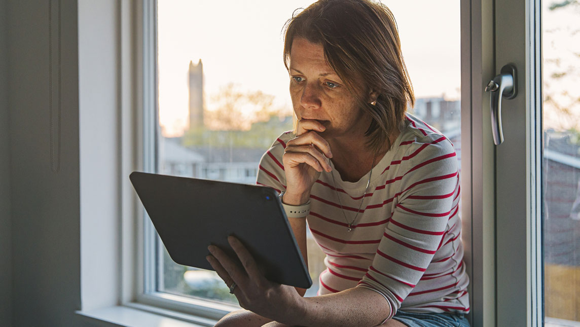 Person sitting in their window using a tablet