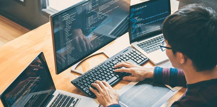 A web developer works across three computer screens writing code.