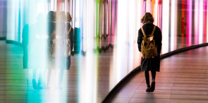 Student walking through illuminated tunnel