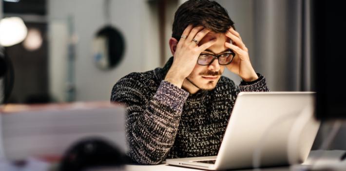 Man working on laptop, looking worried