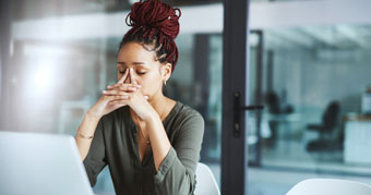 Woman sitting at computer with her hands on her face
