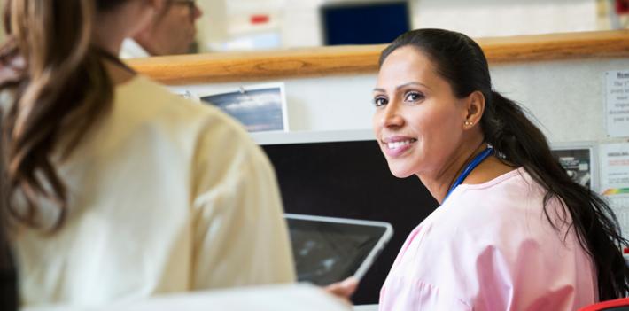 Nurses talking at nurses station using ipad
