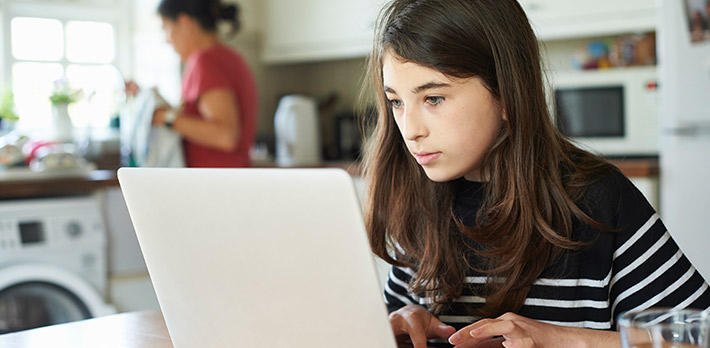 A student attends a remote lesson in their kitchen.