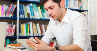 Man using his tablet in a library