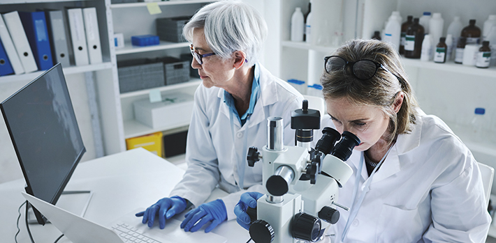 Scientists looking at microscope and laptop