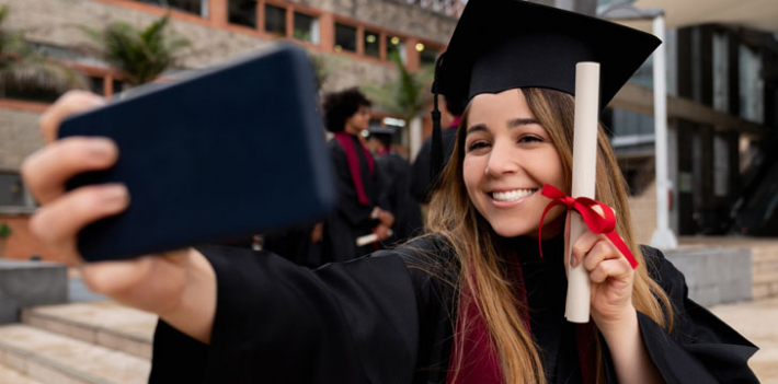 A happy, graduating student taking a selfie, holding their certificate