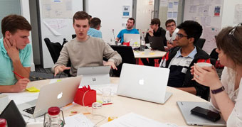 Students working on hackathon pitch
