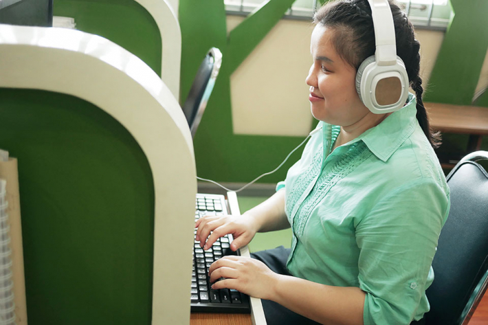 Visually-impaired person working at a computer wearing headphones