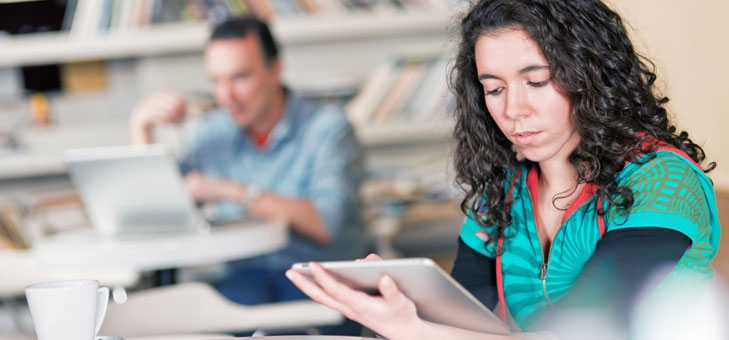 Woman browses on a tablet in a library