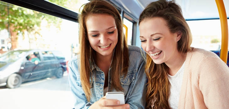 Two women reading a text message on a bus
