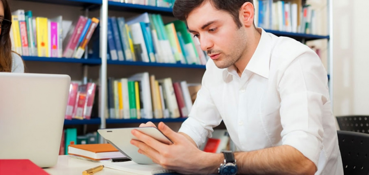 Student using his digital tablet in a library