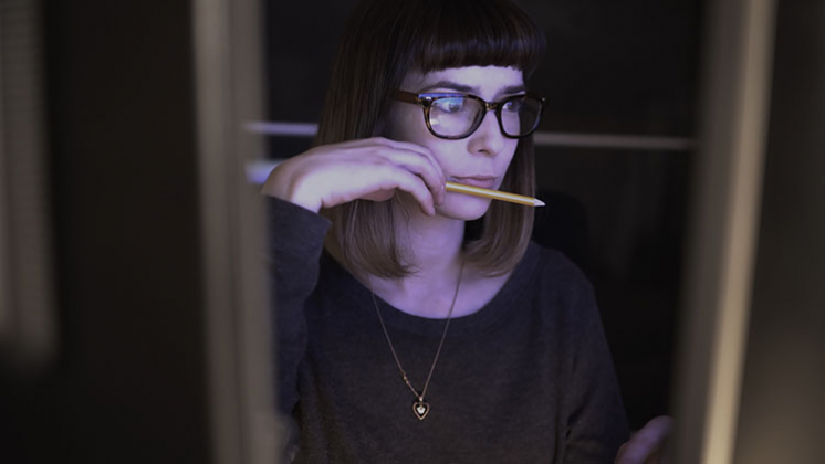 Woman with screen reflection in her glasses